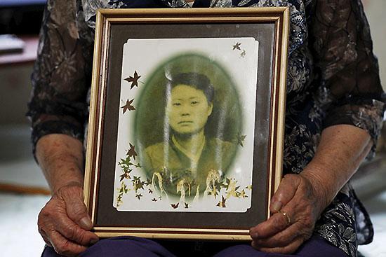<div align=right><font color=blue>ⓒREUTERS</font></div>'위안부' 피해자 이옥선 할머니가 경기도 광주시 '나눔의 집'에서 젊은 시절 사진을 들고 있다.